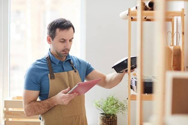 Volwassen man met schort met behulp van digitale tafel tijdens het inventariseren in de voedselbezorgservice