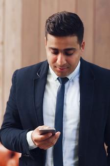 Volwassen man met smartphone in handen.