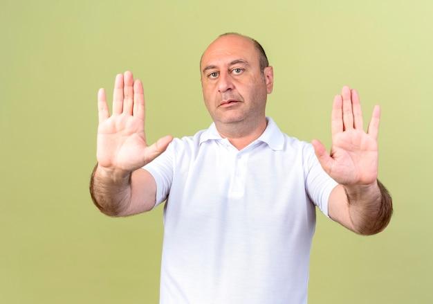 Volwassen man met stop gebaar geïsoleerd op olijfgroen