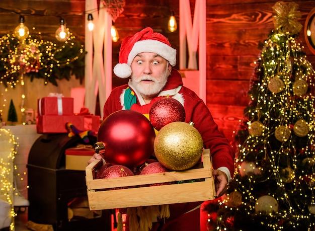 Volwassen man met witte baard. bebaarde grootvader senior man vieren kerst. huis versieren. kerstgeest. kerst decoratie. kerstman. opa met speelgoed. winter korting. oudere mensen.