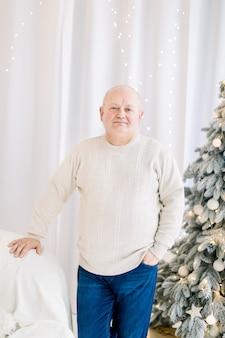 Volwassen man ontspannen thuis op kerstboom achtergrond