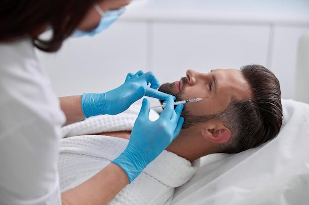 Volwassen man patiënt ligt op de bank en ondergaat de procedure voor het verwijderen van kraaienpootjes in de kliniek