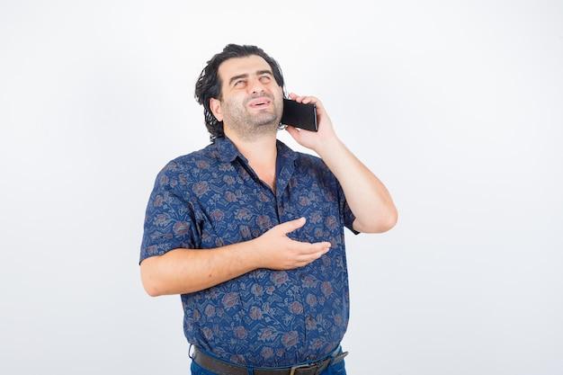 Volwassen man praten op mobiele telefoon in shirt en op zoek gelukkig, vooraanzicht.