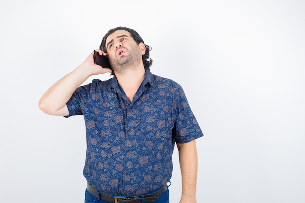 Volwassen man praten op mobiele telefoon in shirt en op zoek ontevreden, vooraanzicht.