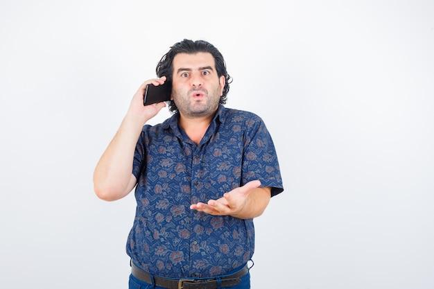Volwassen man praten op mobiele telefoon in shirt en op zoek verbaasd, vooraanzicht.