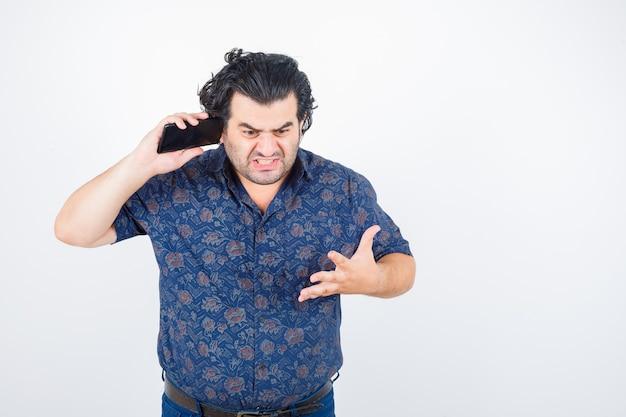 Volwassen man praten op mobiele telefoon in shirt en op zoek woedend, vooraanzicht.