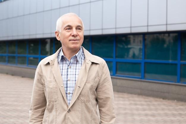 Volwassen man professor of freelancer buiten in stadslandschap in de buurt van kantoorgebouwen