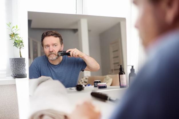 Volwassen man scheert thuis zijn baard af met een elektrisch scheerapparaat tijdens quarantaine. knappe bebaarde man zijn baard trimmen met een trimmer thuis terwijl barbershops gesloten. reflectie in spiegel.