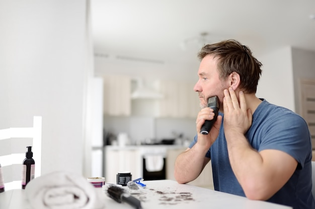 Volwassen man scheert thuis zijn baard af met een elektrisch scheerapparaat