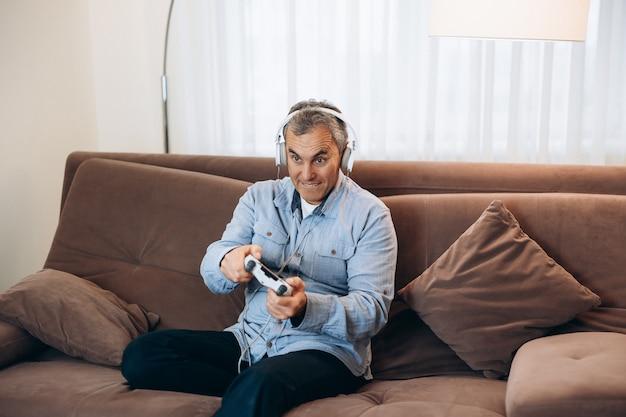 Volwassen man spelen op console. goede tijd op weekendconcept. geconcentreerde man met koptelefoon zittend op een bruine bank, gamecontroller vasthoudend en videogames spelend.