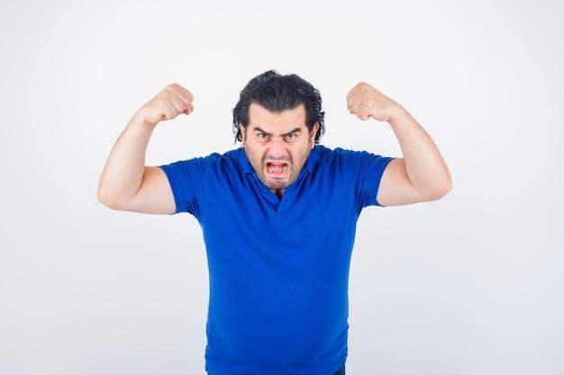 Volwassen man spieren in blauw t-shirt, spijkerbroek tonen en boos kijken
