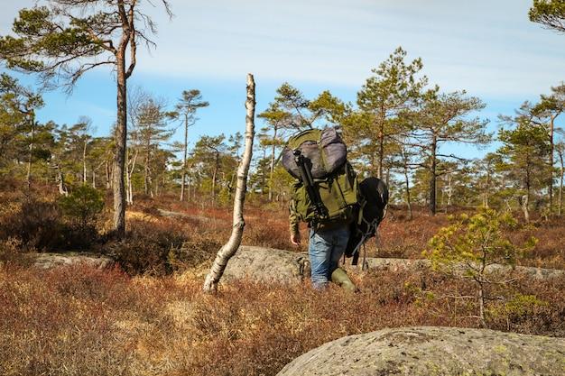 Volwassen man, sterke mannelijke fotograaf die zware rugzakken draagt, het noorse bos in wandelen voor zijn volgende shoot.
