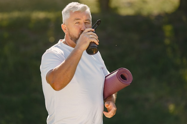 Volwassen man training in een zomerpark. oudste die zich met een mat bevindt. oude man in een sportkleding.