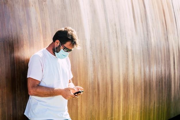Volwassen man typt aan de telefoon en leest nieuws buiten met een blauw beschermend masker