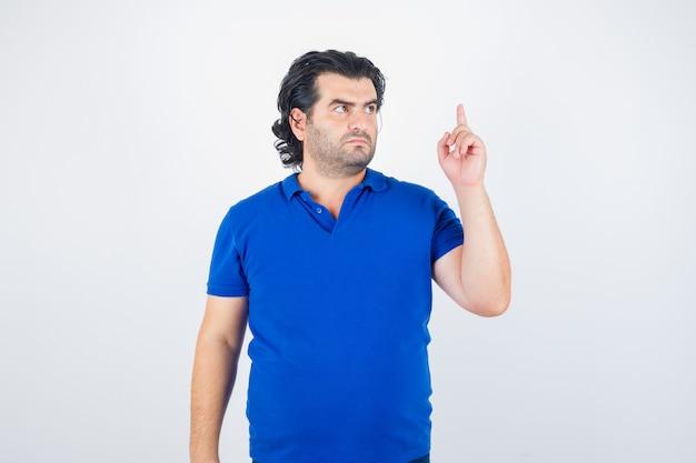 Volwassen man verhogen wijsvinger in eureka gebaar in blauw t-shirt, spijkerbroek en op zoek verstandig, vooraanzicht.