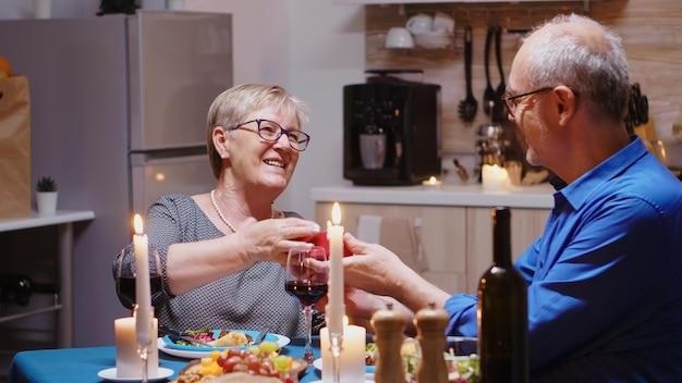 Volwassen man verrassende vrouw met cadeau tijdens fastive diner zittend aan de tafel in de keuken. gelukkig vrolijk bejaarde echtpaar dat samen thuis eet, geniet van de maaltijd, hun jubileum viert