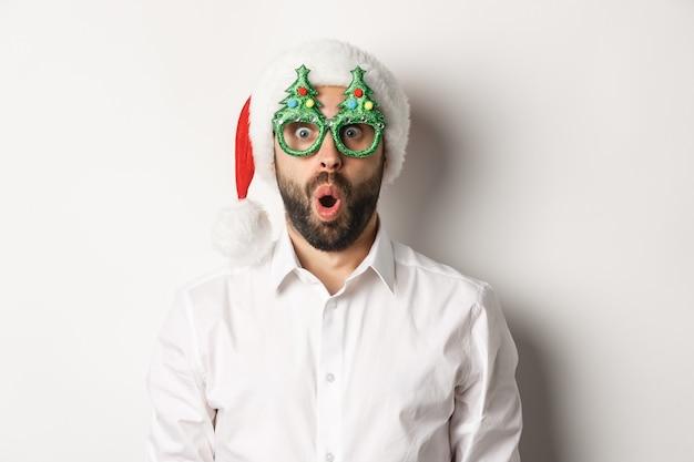 Volwassen man viert wintervakantie, draagt kerstfeest bril en kerstmuts, kijkt verrast camera, staande