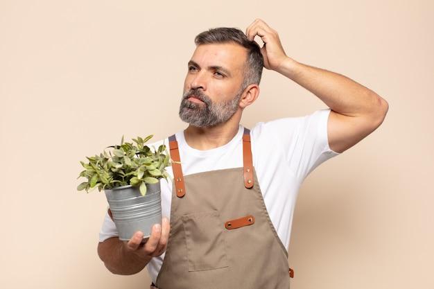 Volwassen man voelt zich verbaasd en verward, krabt aan zijn hoofd en kijkt opzij