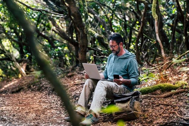Volwassen man werkt met computerlaptop in het midden van het groene wilde bos