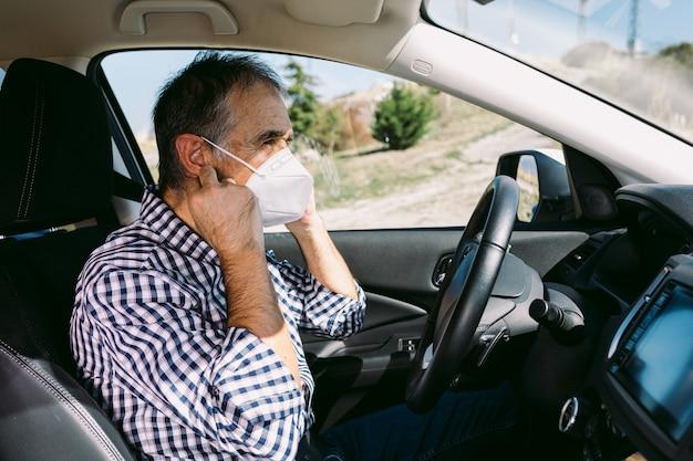 Volwassen man zet masker op in auto om zichzelf tegen covid-19 te beschermen
