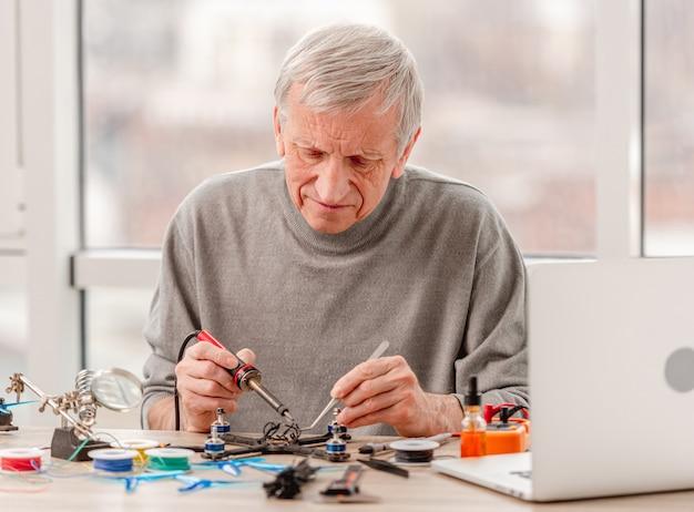 Volwassen man zit door de tafel en draden solderen tijdens het reparatieproces van de quadcopter