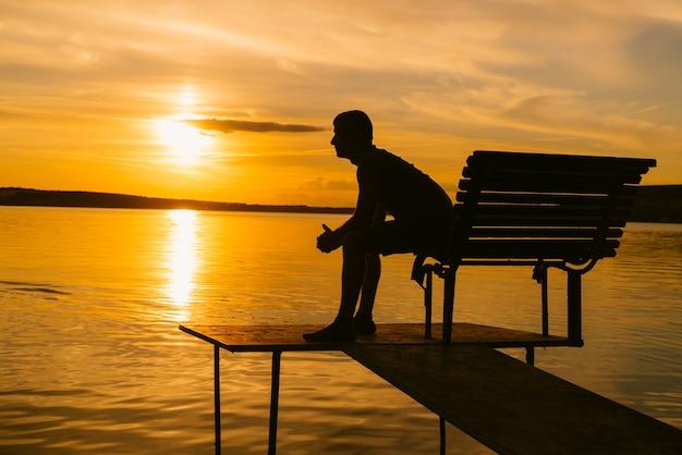 Volwassen man zit op de bank met gevouwen handen op de achtergrond van de rivier bij zonsondergang
