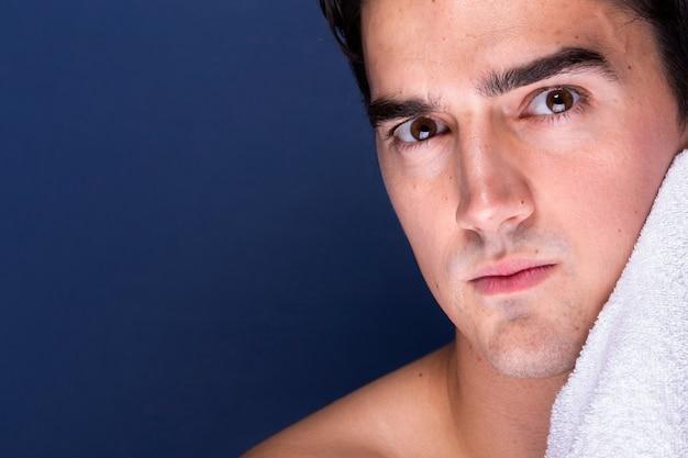 Volwassen mannelijk schoonmakend gezicht met handdoek