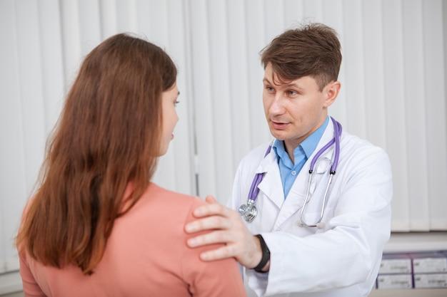 Volwassen mannelijke arts die bij zijn kliniek werkt, die met een vrouwelijke patiënt spreekt. ervaren arts die zijn verstoorde patiënt troost