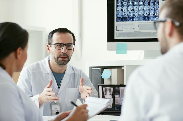 Volwassen mannelijke arts in gesprek met zijn team aan de tafel tijdens een bijeenkomst op kantoor