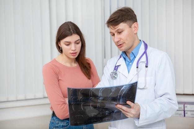 Volwassen mannelijke arts in gesprek met zijn vrouwelijke patiënt, haar mri-scanresultaten uitleggen