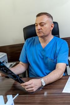 Volwassen mannelijke arts kijken naar x-ray geïsoleerd op moderne kantoor achtergrondkleur. gezondheidszorg, röntgen, mensen en geneeskunde concept.