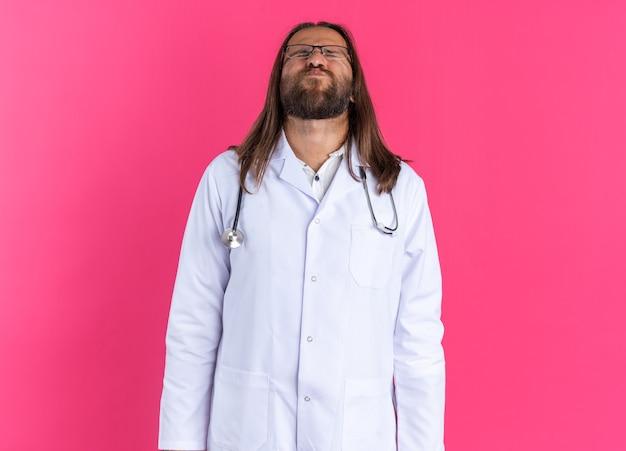 Volwassen mannelijke arts met een medisch gewaad en een stethoscoop met een bril die het hoofd naar achteren kantelt, puffende wangen met gesloten ogen geïsoleerd op een roze muur