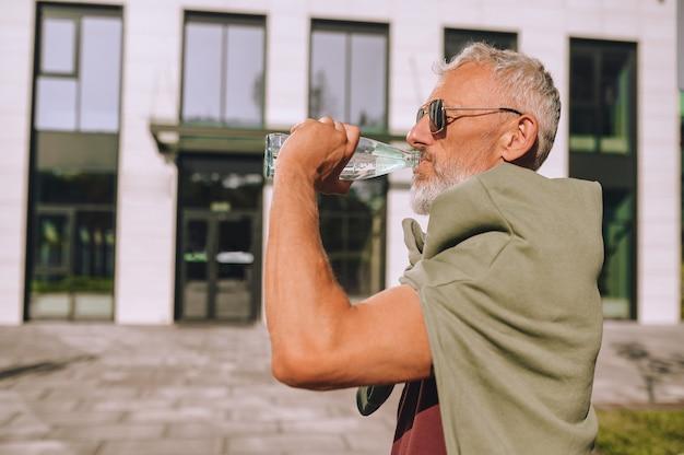 Volwassen mannelijke atleet die de vochtbalans herstelt na de training