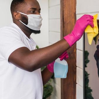 Volwassen mannelijke desinfecterende huis met een doek