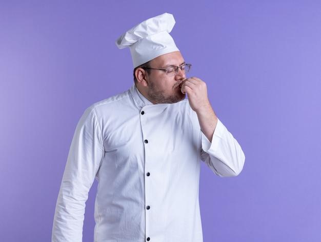 Volwassen mannelijke kok met een uniform van de chef-kok en een bril die de lippen met de hand aanraakt met gesloten ogen geïsoleerd op een paarse muur
