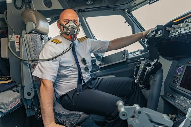 Volwassen mannelijke piloot draagt een luchtmasker in de cockpit van het vliegtuig