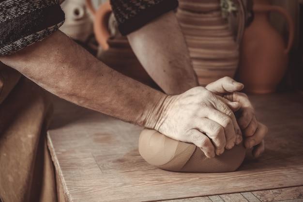 Volwassen mannelijke pottenbakkersmeester die de klei fijnstampen