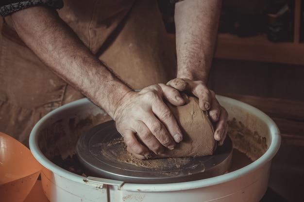Volwassen mannelijke pottenbakkersmeester die de klei stampen