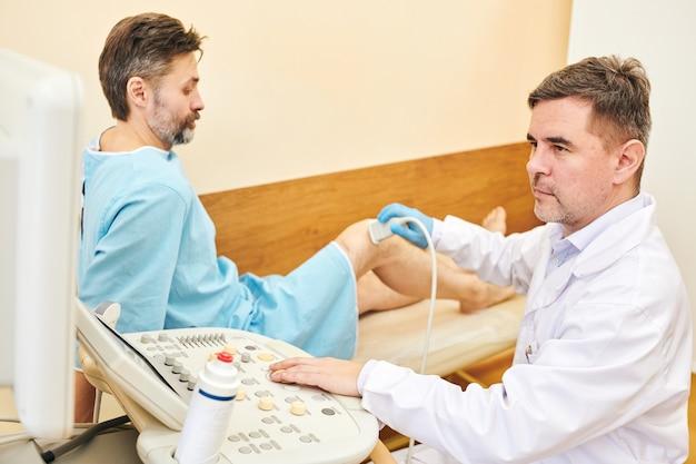 Volwassen mannelijke sonograaf met stoppels met behulp van echografie machine tijdens het onderzoek van de knie van de mens