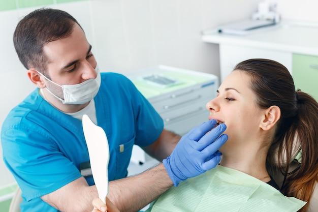Volwassen mannelijke tandarts werken met vrouw patiënt met een spiegel bezoekende tandarts met tandheelkundige controle bij de kliniek tandheelkunde bezetting behandeling medische industrie gezondheidszorg mensen verzekering