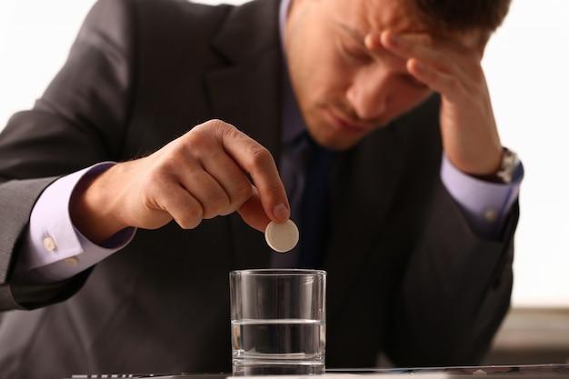 Volwassen mannelijke zakenman die een pijnstiller heeft