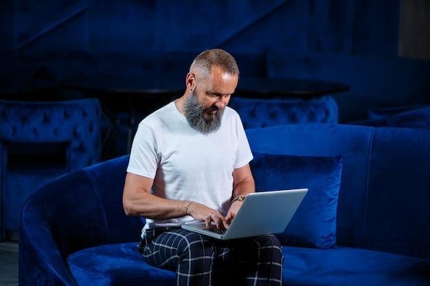 Volwassen mannelijke zakenman, leraar, mentor die aan een nieuw project werkt. zit bij een groot raam op de tafel. hij kijkt naar het scherm van de laptop.