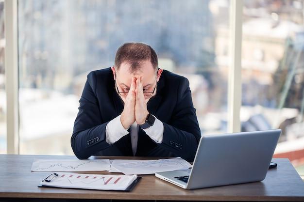 Volwassen mannelijke zakenman, leraar, mentor werkt aan een nieuw project op kantoor en is nerveus. zit aan de tafel bij het grote raam. hij werkt op een laptop, zakelijke problemen