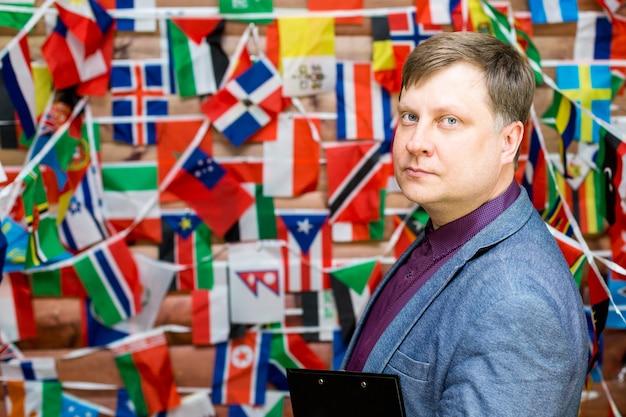 Volwassen mannelijke zakenman met pen en map in handen op de achtergrond van de vlag.
