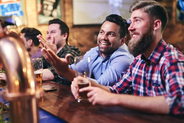 Volwassen mannen kijken naar de voetbalwedstrijd aan de bar