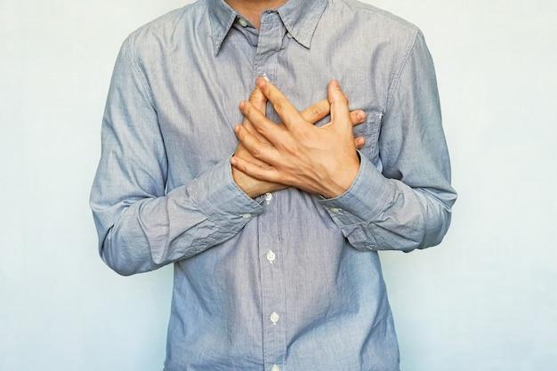 Volwassen mannen met symptomen van een acute terugkerende hartaanval. man vastklampen hart op een blauwe achtergrond. pijn op de borst. pre-infarct angina, hartfalen, angina, tachycardie, pericarditis,