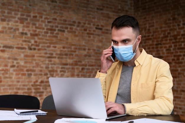 Volwassen mannetje dat een gezichtsmasker draagt op kantoor