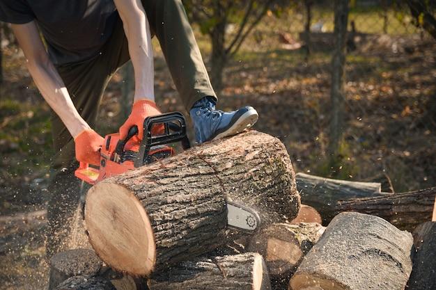Volwassen mannetje dat hout snijdt met een elektrische kettingzaag