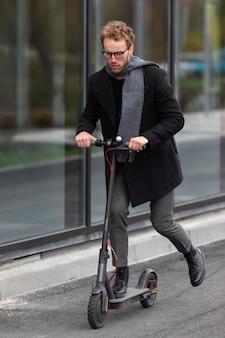 Volwassen mannetje dat zijn elektrische autoped berijdt