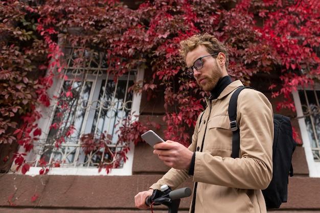 Volwassen mannetje dat zijn mobiele telefoon buitenshuis doorbladert